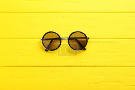 Photo for Black sunglasses on a yellow wooden table, top view - Royalty Free Image