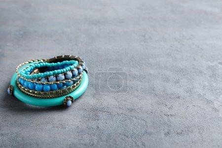 Foto de Hermosas pulseras en una mesa gris - Imagen libre de derechos