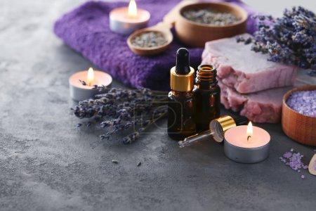 Photo pour Huile de lavande avec du savon, de sel et de fleurs sur table gris - image libre de droit
