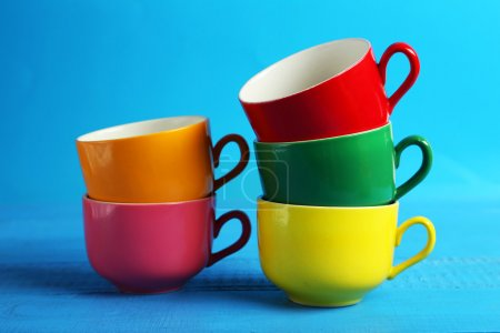 Colorful cups isolated on blue