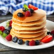 Delicious pancakes with berries on blue wooden bac...