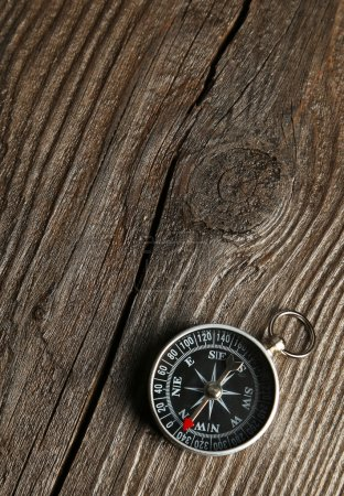 Photo for Compass on brown wooden background - Royalty Free Image