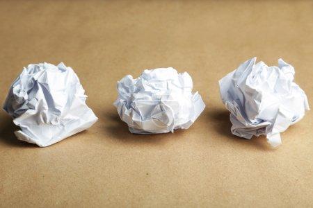 Photo pour Boules de papier froissées sur fond brun - image libre de droit