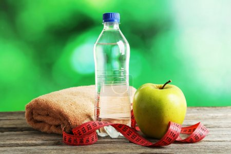 Photo for Green apple with measuring tape and bottle of water on grey wooden background - Royalty Free Image