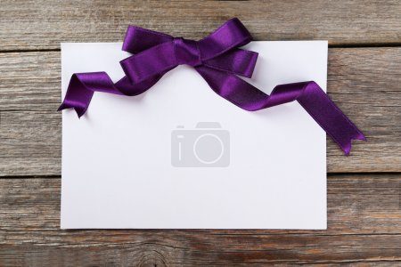 Photo for Blank paper sheet with purple bow on grey wooden background - Royalty Free Image