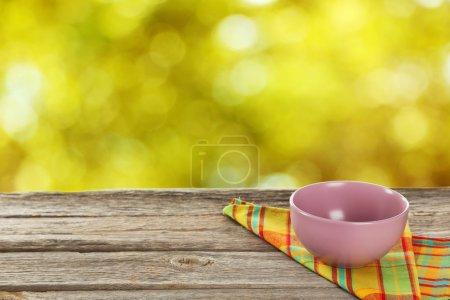 Photo pour Table en bois avec bol de nappe et de violet - image libre de droit