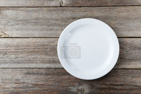 Photo for Empty white plate on grey wooden background - Royalty Free Image