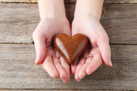 Photo for Woman's hands with chocolate heart on wooden background - Royalty Free Image