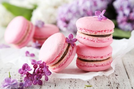 Photo for French pink macaroons with lilac flowers on white wooden background - Royalty Free Image