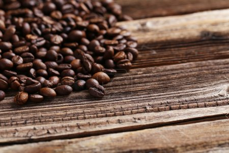 Photo for Roasted coffee beans on a brown wooden background - Royalty Free Image