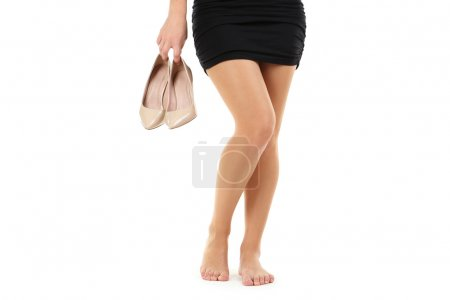 Female legs with beige high-heeled shoes
