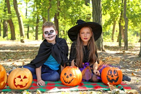 girl witch and little boy with pumpkin
