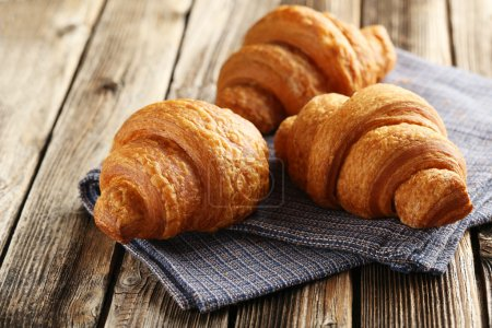 Photo for Tasty fresh croissants on brown wooden background - Royalty Free Image