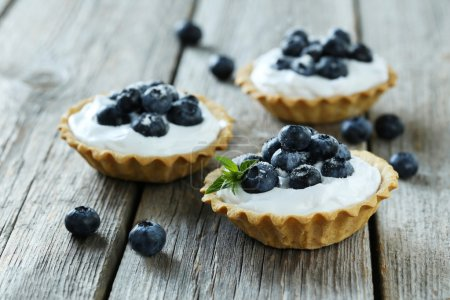 Photo for Dessert tartlets with blueberries on grey wooden background - Royalty Free Image