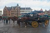 Horse-drawn carriages in Bruges, Belgium. Old Market square Grote markt, Brugge city landscape. Oil painting textured image based on photo