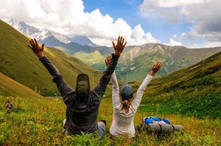 Photo pour Un groupe de touristes avec de grands sacs à dos se détend sur une prairie verte avec vue sur la montagne - image libre de droit