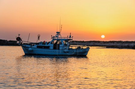 Fishing boat lies at sundown