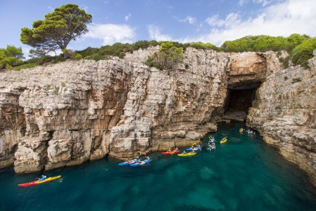 Kayakers at a sea cave at the Lokrum Island in Croatia