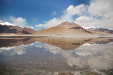 Photo for Landscape of the green lake in Bolivia natural reserve. Mountain range view and blue sky reflecting on the lagoon water. Calm and lonely scenery. - Royalty Free Image