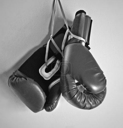 Photo for Black and white boxing gloves hanging on a light wall - Royalty Free Image
