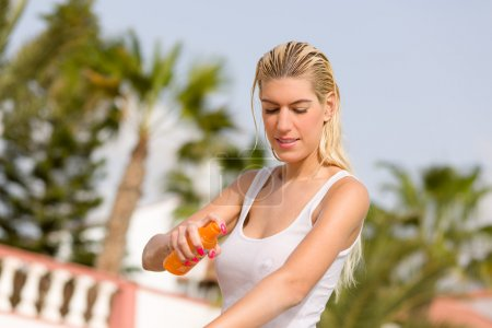 Sexy girl with sunblocker in wet shirt