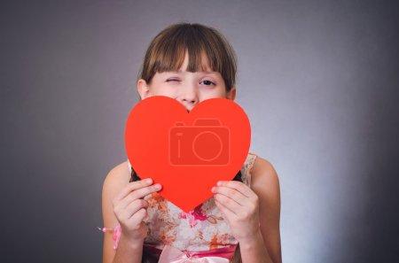 Photo pour La fille claque un œil et ferme un cœur de bouche. Saint-Valentin. 14 février . - image libre de droit