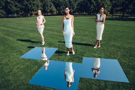Beatiful elegant girls posing on golf course with green grass and mirrors