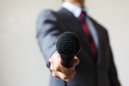 Man in business suit holding a microphone conducting a business