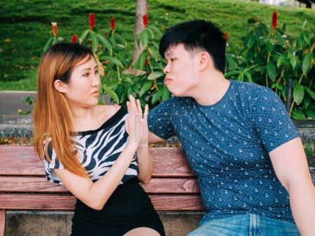 Photo pour Jeune homme asiatique essayant d'embrasser une fille et se fait rejeter - image libre de droit