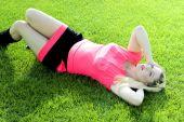 Krásná blondýnka leží na trávě fotbalové hřiště