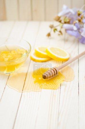 Photo pour Trempette au miel avec nid d'abeille, citron, fleurs et pot sur table en bois clair . - image libre de droit