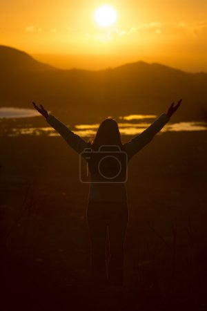 Photo pour Young woman with open arms waiting for the sunrise, slightly noise because of the dificult light situation - image libre de droit