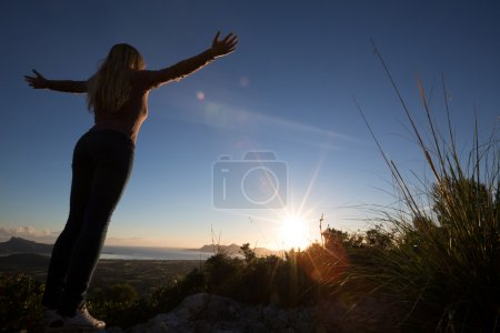 Photo pour Silhouette of young woman with open arms looking to the sunrise - image libre de droit