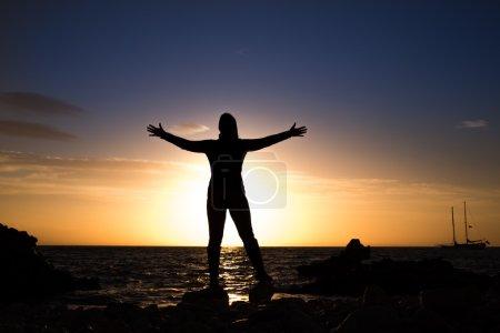 Photo pour Silhouette de femme d'âge mûr à bras ouverts à la recherche de la mer - image libre de droit