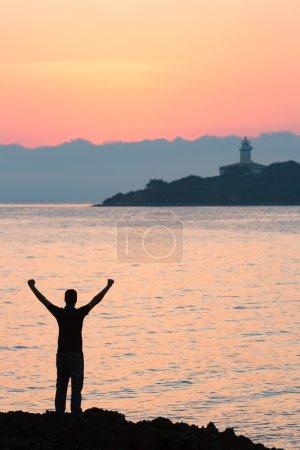 Photo pour Silhouette à bras ouverts à la recherche pour le lever du soleil - image libre de droit