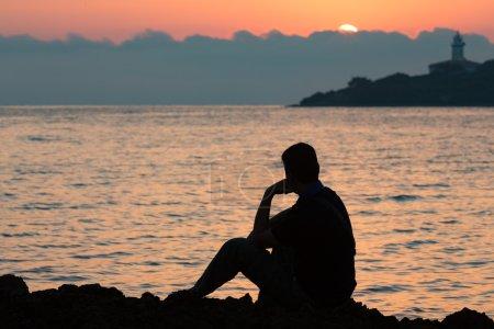 Photo pour Silhouette de l'homme de la pensée dans le lever du soleil, mise au point sélective - image libre de droit