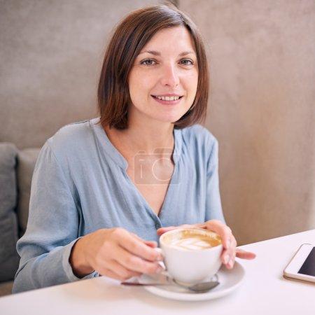 Photo pour Femme caucasienne aux cheveux châtains et un beau top gris souriant tout en regardant la caméra comme elle a les deux mains sur sa tasse matin fraîche de café, sa tablette juste visible sur la table en face de lui - image libre de droit