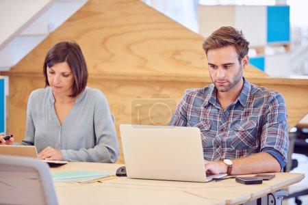 Photo pour Étudiant masculin et féminin travaillant l'un à côté de l'autre dans un espace de co-travail créatif, que l'homme tape sur son ordinateur portable et la femme continue à lire sur sa tablette électronique - image libre de droit