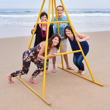 Photo pour Une famille de caucasiens heureux souriant et posant autour d'une structure métallique jaune sur la plage, ils s'aiment et se soucient tellement . - image libre de droit