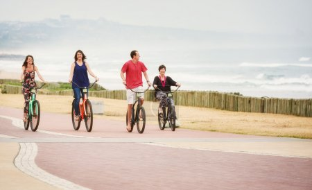 Happy healthy family riding bicycles along the seaside