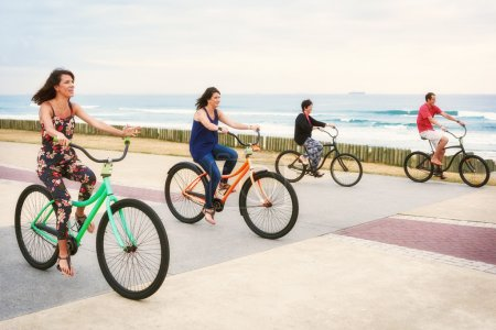 Mother cycling with her three children on the promenade