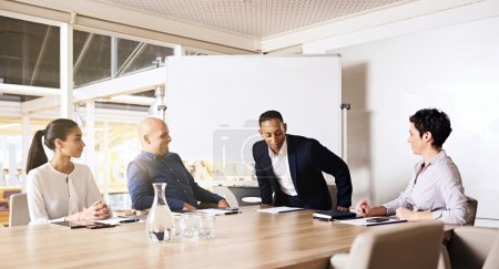 Photo pour Hommes d'affaires à la réunion, homme d'affaires assis à la tête d'une table de conseil d'administration à côté d'une de ses collègues féminines, prêt à collaborer avec les 3 autres dirigeants d'entreprise qui étaient déjà assis, attendant et prêts - image libre de droit