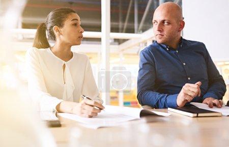Photo pour Homme d'affaires caucasien accordant une attention particulière à son partenaire d'affaires féminin comme elle continue à expliquer les détails de sa nouvelle proposition d'acquisition de leur entreprise rivale . - image libre de droit