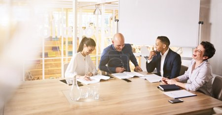 Business professionals laughing during meeting