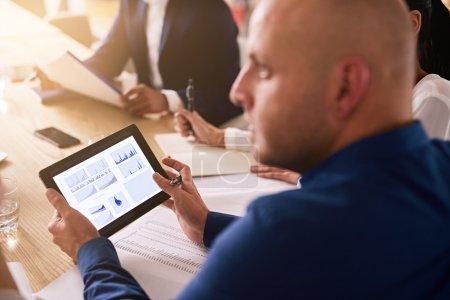 Photo pour Tablette utilisée dans une réunion d'affaires avec des graphiques sur l'écran par un homme d'affaires caucasien portant une chemise bleue pour fournir une analyse financière en direct . - image libre de droit
