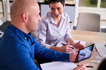 Photo pour Femme d'affaires caucasienne mature souriant à son collègue masculin tenant une tablette avec des graphiques affichés à l'écran lors de leur réunion ensemble . - image libre de droit