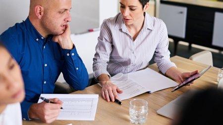 Mature businesswoman asking business colleague