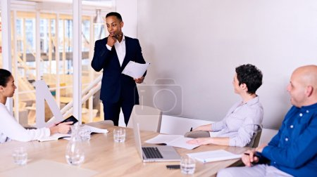 Businessman standing in front of 3 colleagues