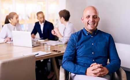 Businessman laughing in front of colleagues