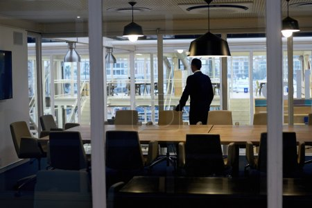 businessman standing alone in conference room